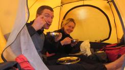 A couple relishing their meal inside a tent