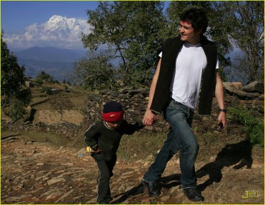 Orland Bloom holding hands with local boy in nepal