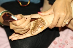 Woman putting mehndi on her palm