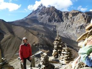 Un trekker que presenta en Thorong Pass