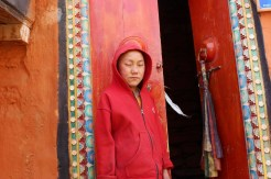 A young monk-to-be guarding the monastery door at Lo Manthan, Mustang